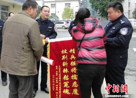 邓爱毕之妻吴海平给警方赠予锦旗。 谢朝军 摄