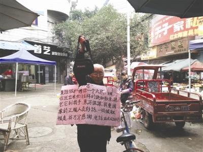 程大爷在武胜街头举牌寻找包的主人