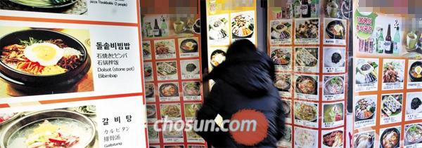 12日,在明洞陌头,一位旅客正在检察遍及陌头的餐馆菜单。(韩国《朝鲜日报》网站)