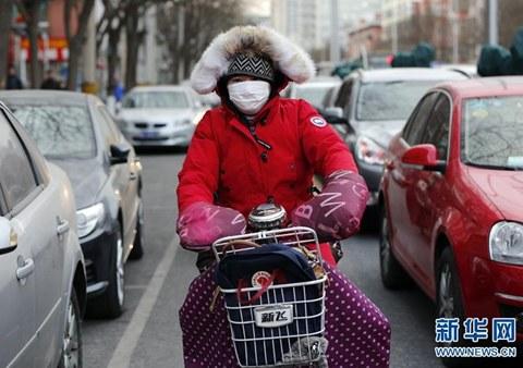 """1月22日,寒流大部�已�_到都城,市民""""全部武�b""""地在北京陌�^�T�出行。�D像��v:新�A社�者 沈伯�n/�z"""