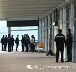 飞机行将到达,香港警方在廊桥外等待。