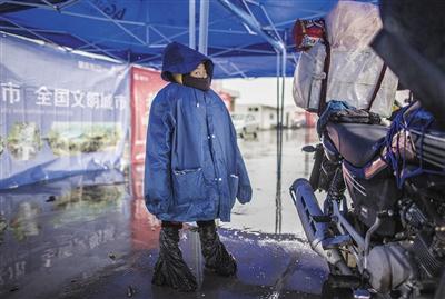 7岁的晓虹跟随父亲从佛山出发回广西,尽管全身防护,但行进4小时后,她的鞋被雨雪完全浸湿。