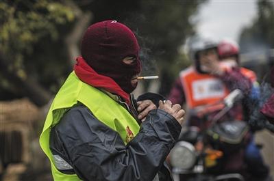 在公路疾驰6小时后,老杨卸下头盔,为了保暖,戴着面罩吸烟。