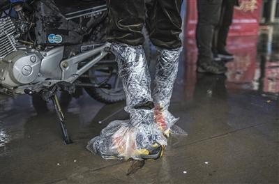 一名骑行者将袋子绑在鞋子外侧,防止鞋被雨水打湿。