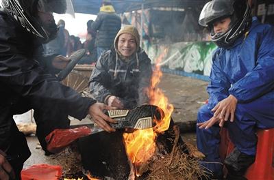 路边休息时,一名摩托车手将湿透的鞋子在火上烘烤。
