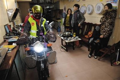 1月24日晚,广西桂平石龙镇,从广东出发的三对夫妇将摩托车停放在旅馆老板的灯具店,店员惊讶地看着闯入的摩托车。
