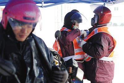 1月24日中午,321国道德庆县,一名妇女正在给自己的骑士丈夫穿雨衣抵御风雨。