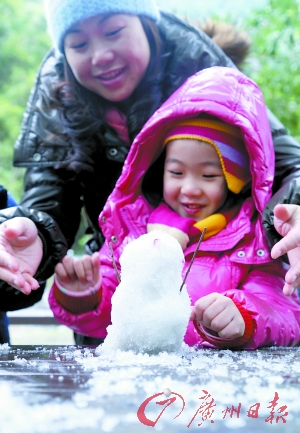 """谢岗银瓶山上,孩子开心地""""堆""""了个小雪人。广州日报记者董哲 通讯员刘建飞摄"""