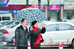 """中午时分,漫天冰珠飞舞,市民走在""""雪花""""中。广州日报记者陈枫摄"""