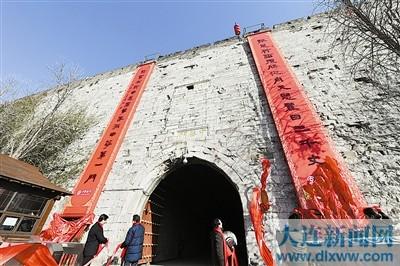 """1月24日,""""城门挂春联,古都开门红""""活动在南京明城墙中华门举行,一副长达15米的大红春联挂上中华门南门。这是南京明城墙650年历史上首次挂出春联。"""