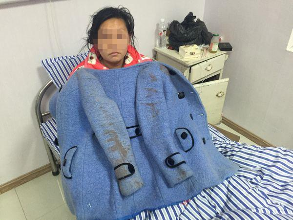 沿河县医院,陈霞一脸乌青的拿着案发当日沾满血迹的外衣