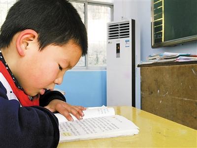 岔河村小学三年级,学生正在开着空调的教室内上课。