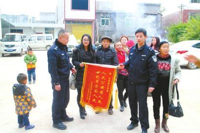 冯利��(左二)与家人为派出所送来锦旗
