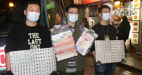 探员展示检获的麻雀及赌款。香港《明报》网站/伍浦锋 摄