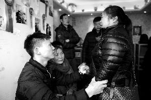 25岁的青年大巧(左)固然无奈谈话,还不断抚慰落泪的亲人。北京晨报记者 郝笑天/摄