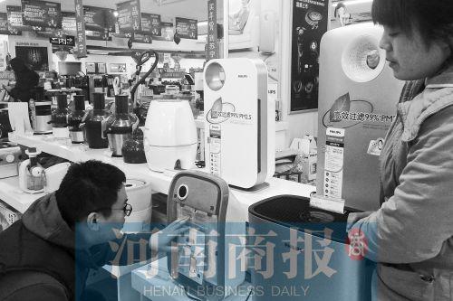 一顾客正在商场选购空气净化器