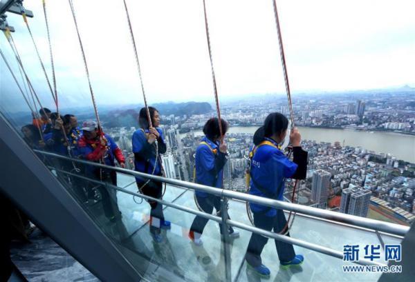 新华社照片,柳州广西,2015年12月6日 广西柳州:303米楼顶建高空玻璃栈道 12月6日,游客在广西柳州云顶观光景点体验高空玻璃栈道。