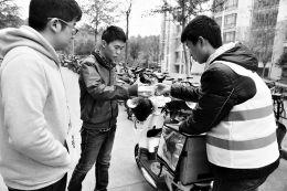 一名订餐的学生从派送员手中接过外卖餐食 东方IC供图