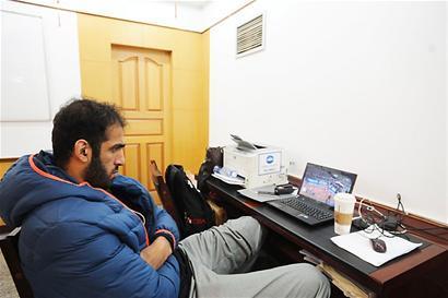 哈达迪在媒体室用电脑观看比赛