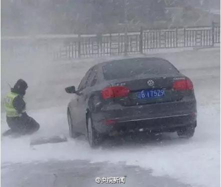 大连交警雪中帮推车 因太累马路上跪倒休息(图)