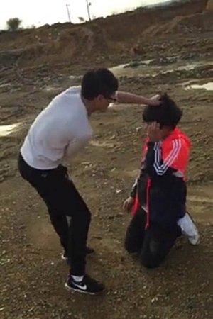 受害男生跪在沙地上,被一白衣男生揪住头发。视频截图