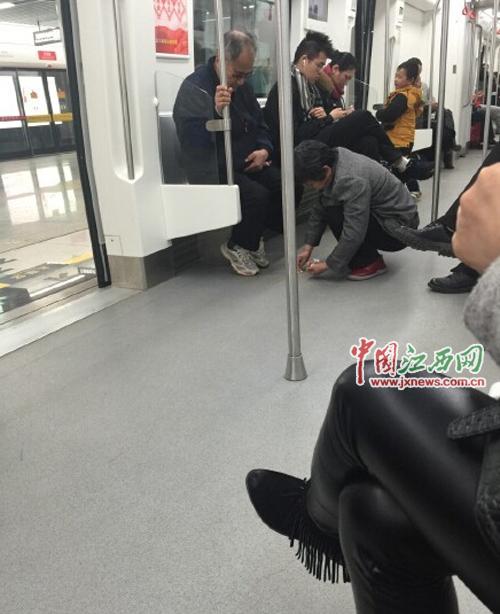 南昌大妈地铁上捡拾泥土 网友:中国好大妈