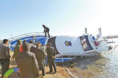 """""""龙湖1号""""被打捞上岸,生产厂家负责人查看船只受损情况。"""
