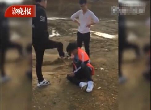 网传视频中,一名身穿红黑色外套的男生跪在地上,一名穿白色上衣的男生和一名穿黑色外套的男生对其轮番掌掴、踢打。(图片来源于网络)