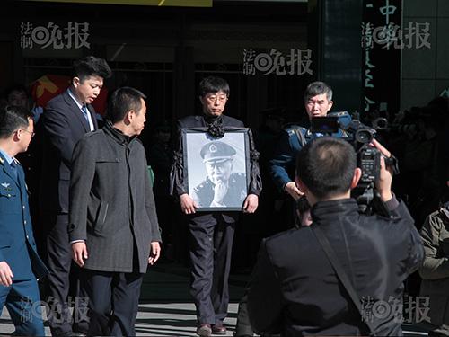 阎宇抱着父亲遗像走出悼念会大厅