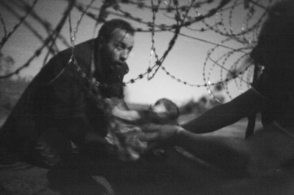 2015年8月28日,匈牙利塞尔维亚边境,一位男人把婴儿从铁丝网下递过。 Warren Richardson