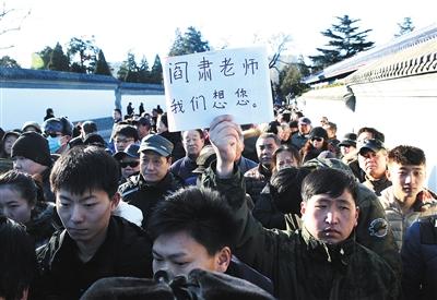 """殡仪馆门口,送别阎老的群众队伍里,一男子举着写有""""阎肃老师我们想您""""的标牌。"""