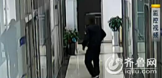 监控视频中,一名黑衣男子先是在走廊里四处观察,然后从容的进了办公室。(视频截图)