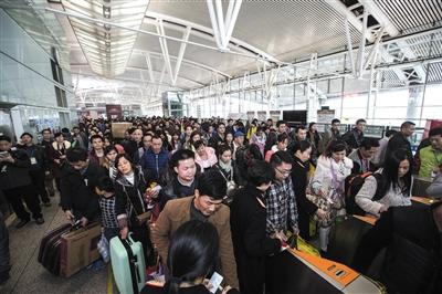 1月31日,广州南站迎来返乡高峰。返乡人员在广州南站进站口等候进站乘车。图/CFP