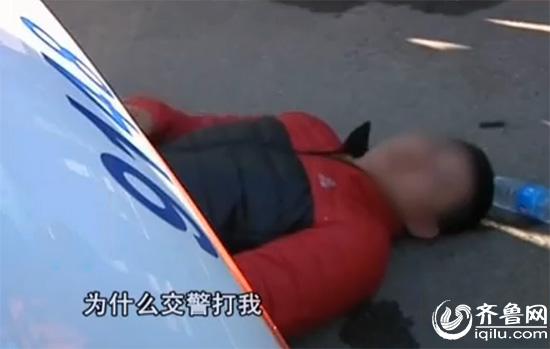 无证无牌酒驾被查,摩托车司机爬到警车下宣称被交警殴伤(视频截图)