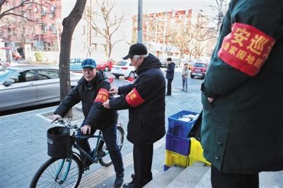 2016年2月19日,潘故里社区,一名治安自愿者在帮火伴整顿袖标。新京报记者 王嘉宁 摄