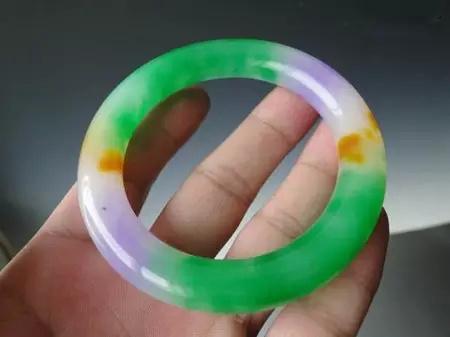 三色翡翠手镯 指的是玉镯上有三种颜色,最好三色是红,绿,紫,这是比较