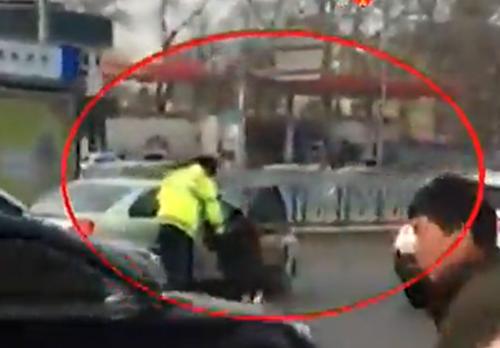 女子就在路边大闹,一度阻碍交通。而交警边劝阻边维持现场交通秩序。(视频截图)