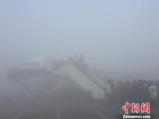 图为乘客在大雾中登机。 雷洋 摄