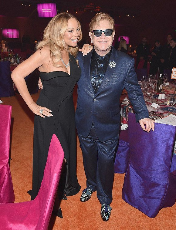 准备了一个晚上:玛利亚・凯莉热情地欢迎宴会主持人埃尔顿,他穿着一件闪亮的深蓝色西装和配套的衬衫,鞋子很醒目。