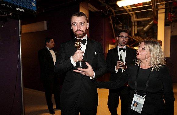 保护:山姆・史密斯离开杜比剧院时用保护的姿态紧紧握住自己的奖杯