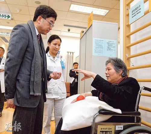 香港食物及卫生局长高永文(左)昨参观明爱医院怀明楼骨科复康病房。他指流感高峰未到顶,建议学校继续为学生量体温。(图自香港《明报》)