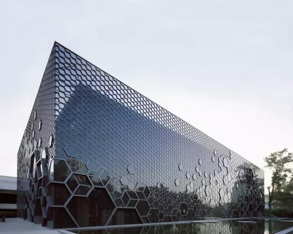 历史的东西仍然在,六边形钢结构重叠组合的玻璃幕墙,在旧有建筑外构筑