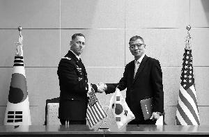 韩国国防部国防方针室室长柳济昇(右)和美国陆军第八团体军司令托马斯·范达尔签订协定后握手。新华/纽西斯