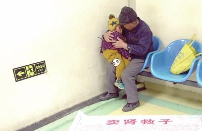 孩儿与养父在病院内期待查验后果。(材料图像)京华时报记者陶冉摄