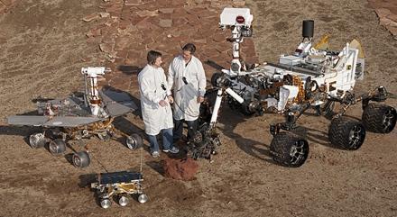 左起第一个为机遇号火星车,第二个像一个玩具车,它是探路者号,中间为工程师,最右边的是好奇号火星车,好奇号没有使用太阳能面板,依靠核电池供电,你瞧它那块头!
