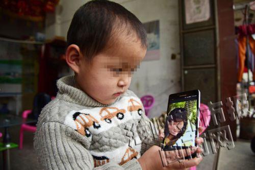 5岁的贤贤想妈妈时,只能通过手机看照片