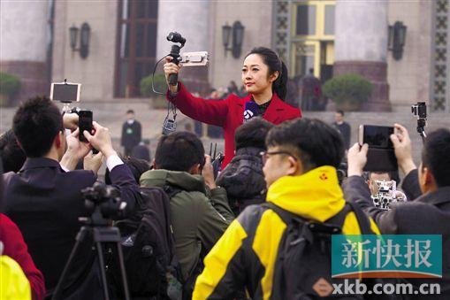 人民大会堂前,一位女记者持自拍稳定器直播,独自进行拍摄采访。