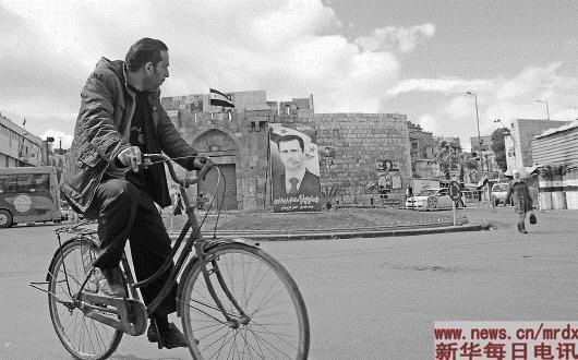 3月15日,叙利亚首都大马士革老城巴卜图玛,一名男子骑车经过。15日早晨,叙利亚首都大马士革上空飘着乌云,不时下起雨来,已经转暖的天气变得有些阴冷。好在这样的天气没有持续多久便艳阳高照,晴空万里。一切看似平静。只有不时从身边经过的身着迷彩服的士兵,随处都会遇到的检查点,以及一些建筑周边设有的路障,才会提醒我们身处一个战乱国家。