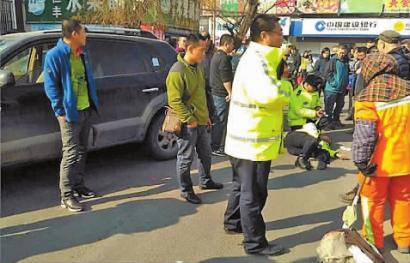 杨学志倒在地上,同事正在照顾他