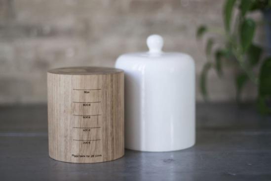 它彩原木制作的圆柱体和洁白的手工陶瓷盖组成,随着从顶部投下来的